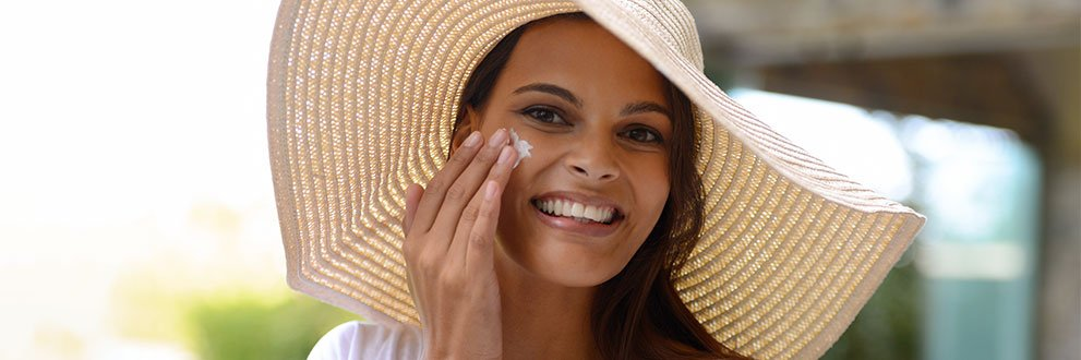 woman with large sunhat on putting sunscreen on her face