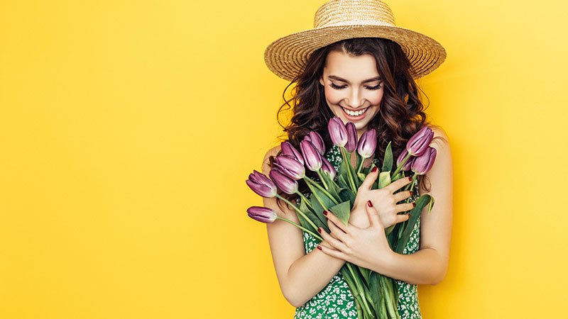 smiling woman standing in front of flowers