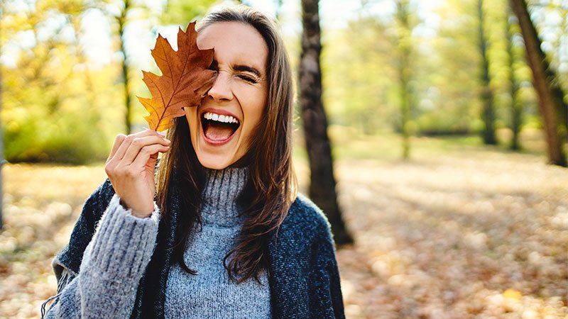 woman outside in the fall smiling with a leaf in front of her eye